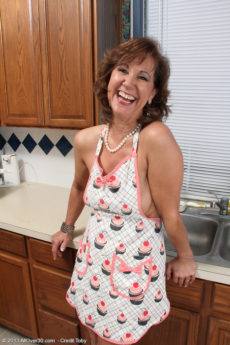 Sexy over 50 housewife Lynn hoses down her saggy breasts at the sink