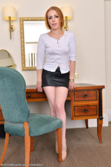Hot redhead secretary Tia Jones lefts her leather skirt to show her natural red pussy hair
