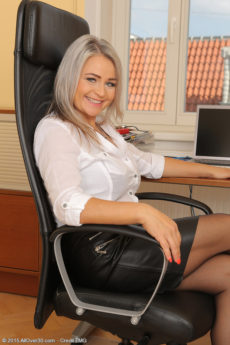 Curvy blonde secretary MILF Zaira Connor lifts her skirt to show her fat pussy lips