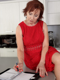 Busty redhead grandma Danny Bloom gets banged by a younger guy in the kitchen