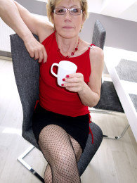 Mature blonde secretary Georgina C in stockings and glasses gets nude in the office