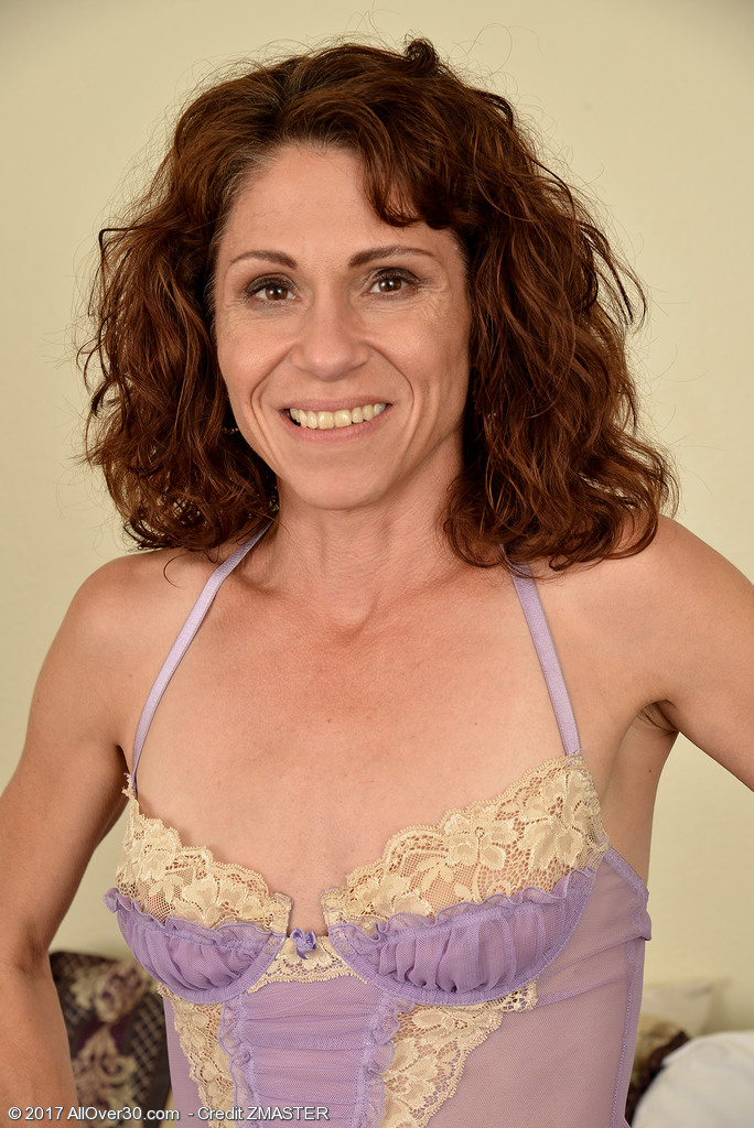 Skinny Redhead MILF Sage Quest Strips Naked and Barefoot On The Bed