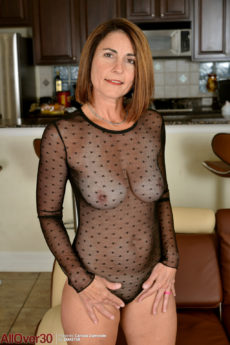Lovely mature woman Carissa Dumonde takes off her body stocking and fingers her pussy