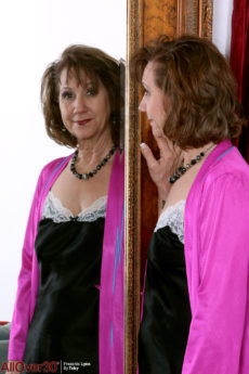 Beautiful over 50 woman Lynn takes off her lingerie in front of a mirror