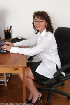 Mature brunette secretary Alanah wearing glasses and her panties at work