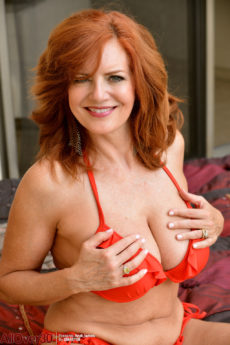 Smiling 60 plus buxom redhead Andi James nude and loving it