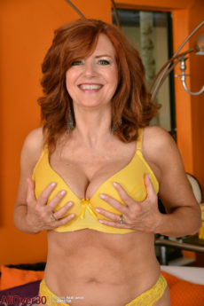Busty redheaded MILF Andi James takes off her yellow bra and panties