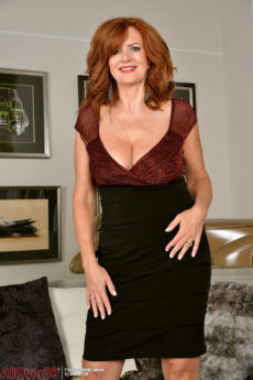 Voluptuous redhead Andi James lifts her skirt to pet her pussy