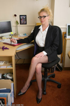Blonde secretary Taya shows off her big breasts in her office