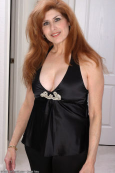 Curvy 40 something redhead Nadine revealing her big tits and furry pussy