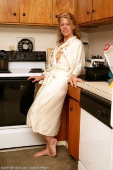Blonde mature housewife Lauren E gets naked in the kitchen