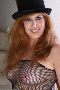 Redhead 59 year old hottie Nadine plays with her feet in fishnet body stockings
