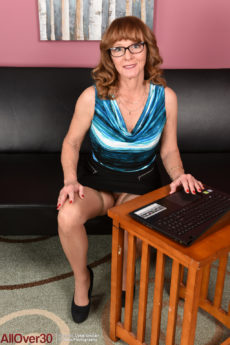 51 year old redhead knockout Cyndi Sinclair playfully gets nude in the living room