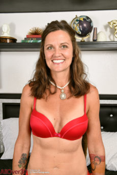 41 year old brunette looker CJ peels off her red bra and panties to pose in stockings